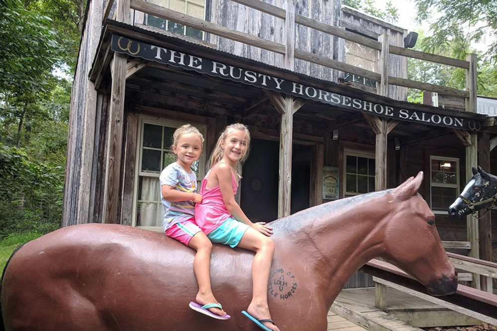 Kids on Horseback in Western Town at Land of Little Horses Animal Theme Park